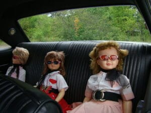 Dolls on the back seat of old car